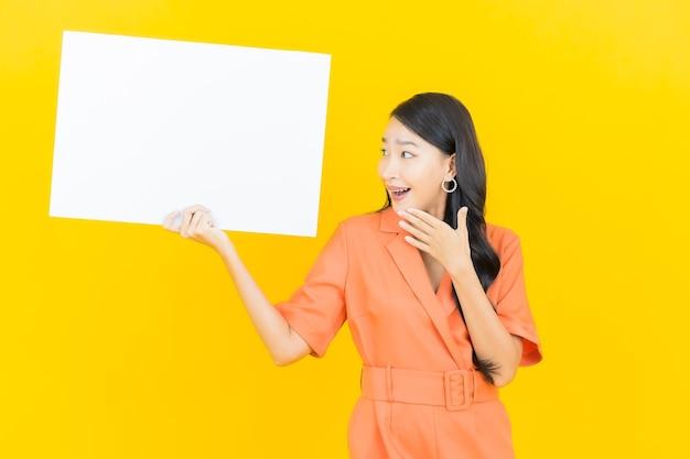 Porträt schöne junge asiatische frau lächeln mit leeren weißen plakatwand auf gelb