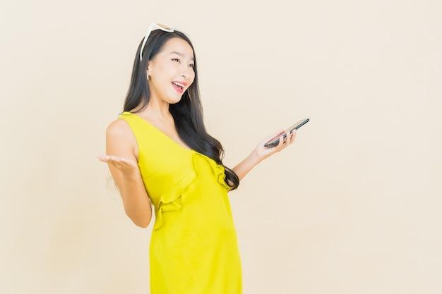 Porträt schöne junge asiatische frau lächeln mit smart-handy auf farbwand