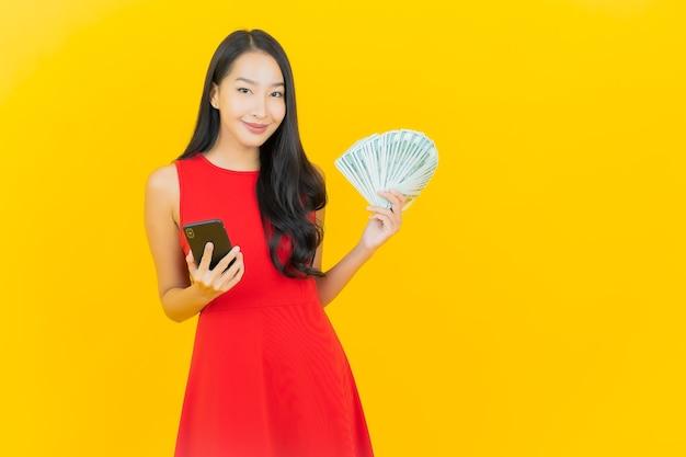 Porträt schöne junge asiatische frau lächeln mit viel geld und geld auf gelber wand