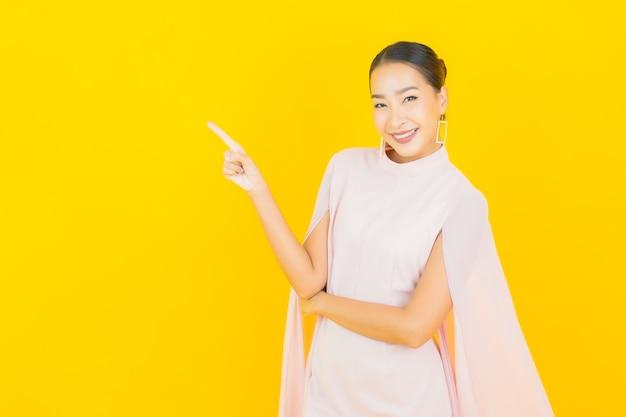 Porträt schöne junge asiatische frau lächeln mit vielen aktion auf gelber wand