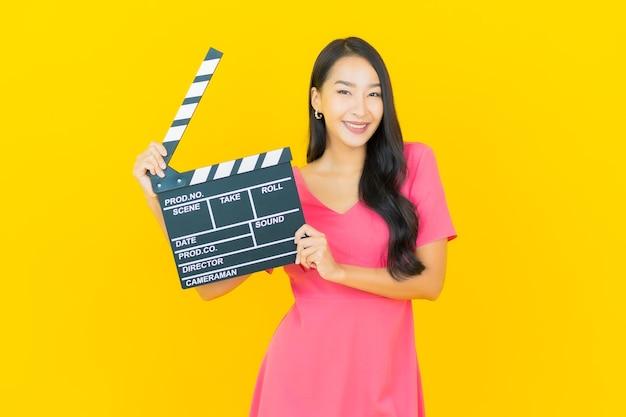 Porträt schöne junge asiatische frau lächelt mit filmschieferplatte, die auf gelber wand schneidet