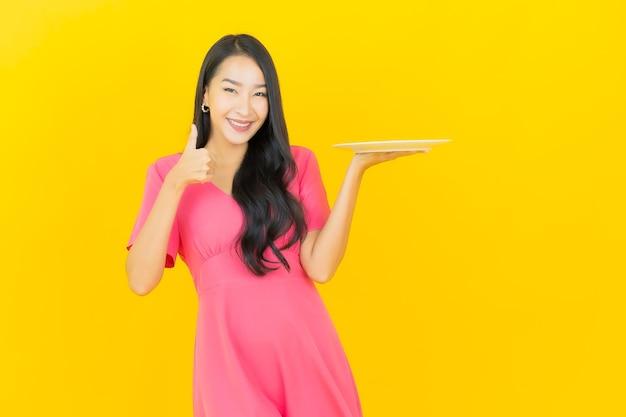 Porträt schöne junge asiatische frau lächelt mit leerem teller teller auf gelber wand