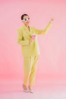 Porträt schöne junge asiatische frau mit 3d-brille und popcorn bereit für film auf farbe zu sehen