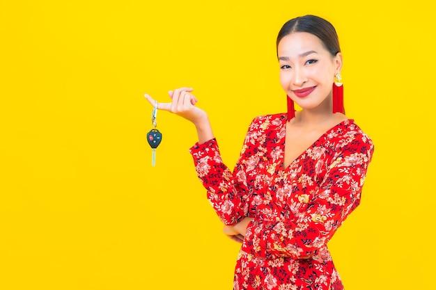 Porträt schöne junge asiatische frau mit autoschlüssel auf gelber wand