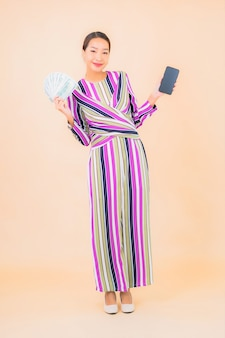 Porträt schöne junge asiatische frau mit bargeld oder geld und mobilem smartphone auf farbe