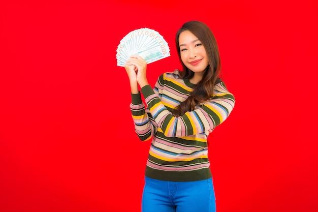 Porträt schöne junge asiatische frau mit bargeld und handy auf roter wand