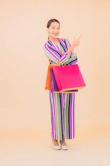 Porträt schöne junge asiatische frau mit bunter einkaufstasche auf farbe