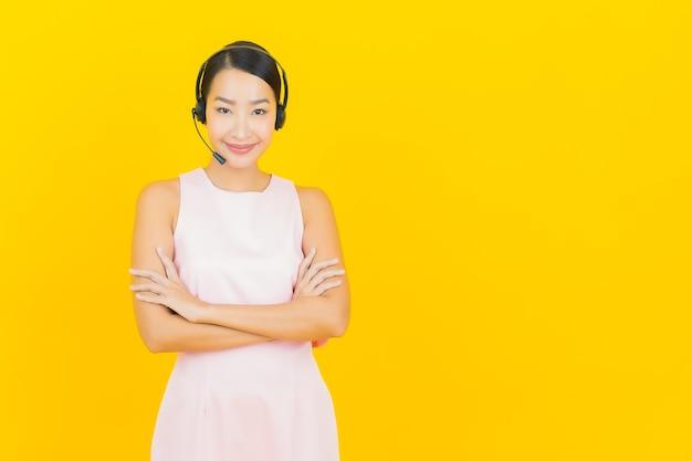 Porträt schöne junge asiatische frau mit call-center-kundendienst-service-center auf gelb