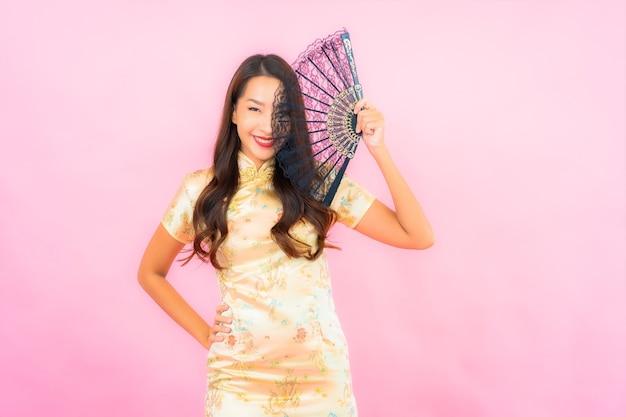 Porträt schöne junge asiatische frau mit chinesischem neujahrskonzept und fächer auf farbwand