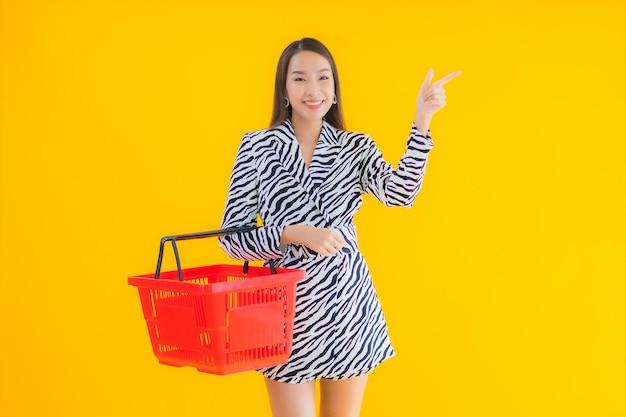 Porträt schöne junge asiatische frau mit einkaufskorb zum einkaufen auf gelb
