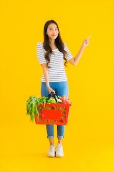 Porträt schöne junge asiatische frau mit einkaufskorbwagen vom supermarkt im einkaufszentrum