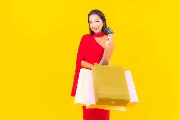 Porträt schöne junge asiatische frau mit einkaufstasche und kreditkarte