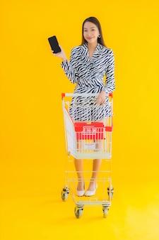 Porträt schöne junge asiatische frau mit einkaufswagen für lebensmitteleinkauf auf gelb