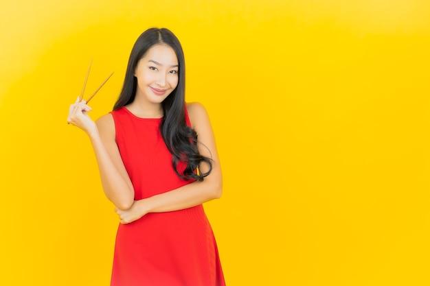Porträt schöne junge asiatische frau mit essstäbchen bereit zu essen auf gelber wand