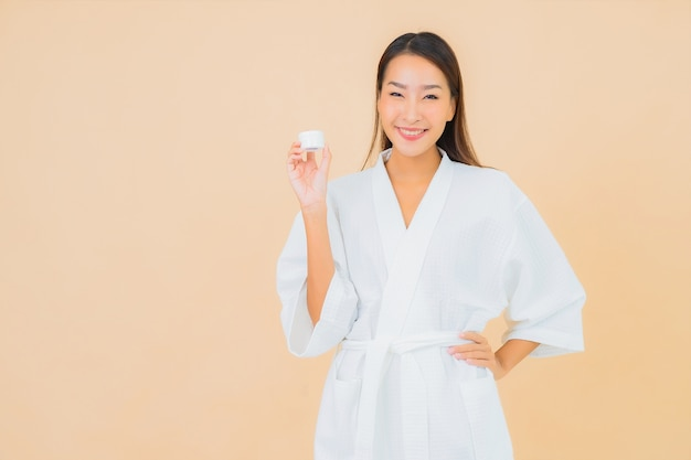 Porträt schöne junge asiatische frau mit flaschenlotion und gesichtscreme auf beige