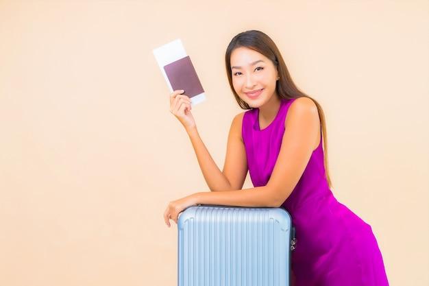 Porträt schöne junge asiatische frau mit gepäck und flugticket auf farbhintergrund
