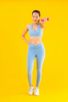 Porträt schöne junge asiatische frau mit hantel und sportbekleidung auf gelb