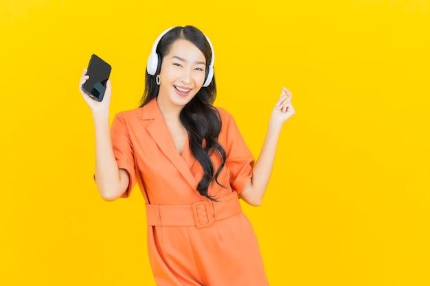 Porträt schöne junge asiatische frau mit headset und smart-handy hören musik auf gelb