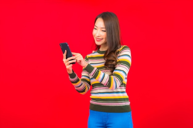 Porträt schöne junge asiatische frau mit intelligentem handy auf roter wand