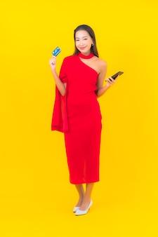 Porträt schöne junge asiatische frau mit intelligentem handy mit kreditkarte