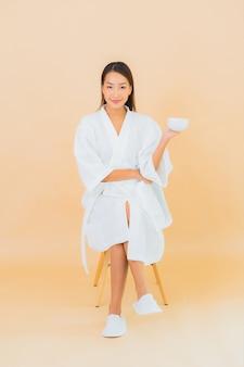 Porträt schöne junge asiatische frau mit kaffeetasse auf beige