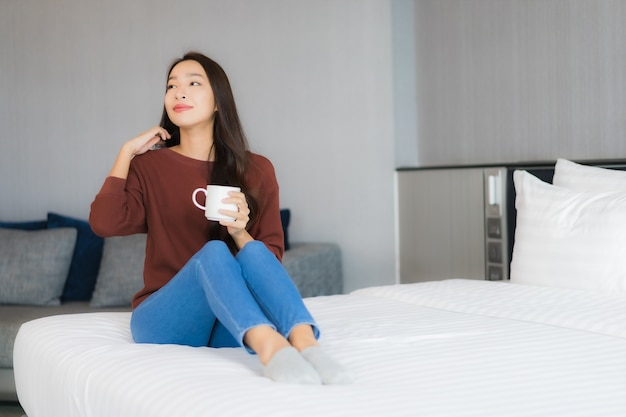 Porträt schöne junge asiatische frau mit kaffeetasse auf bett im schlafzimmer interieur