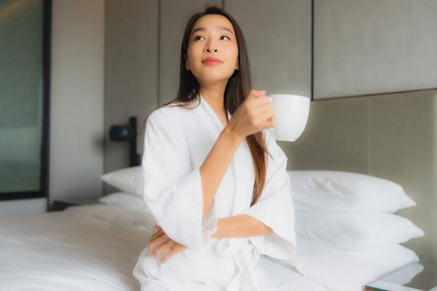 Porträt schöne junge asiatische frau mit kaffeetasse im schlafzimmer