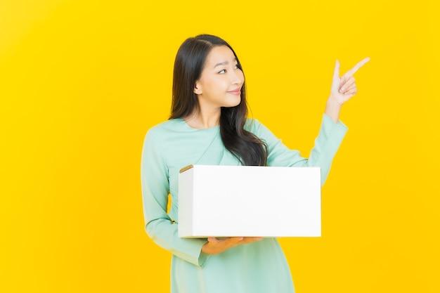 Porträt schöne junge asiatische frau mit karton versandfertig auf gelb