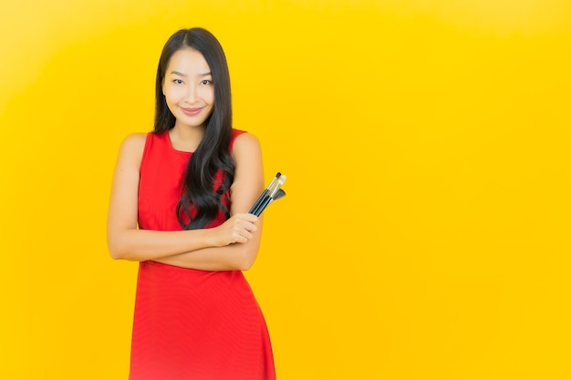 Porträt schöne junge asiatische frau mit kosmetikpinsel auf gelber wand