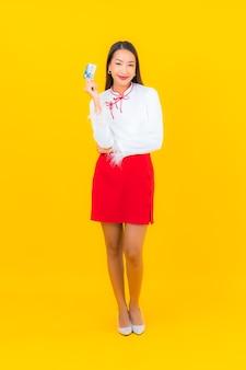 Porträt schöne junge asiatische frau mit kreditkarte für online-shopping auf gelb
