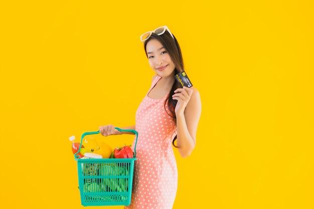Porträt schöne junge asiatische frau mit lebensmittelgeschäft im korb einkaufen vom supermarkt
