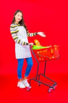 Porträt schöne junge asiatische frau mit lebensmittelkorb vom supermarkt auf roter isolierter wand
