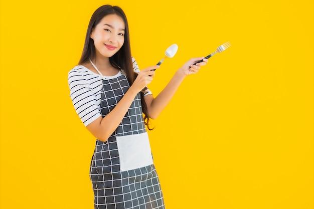 Porträt schöne junge asiatische frau mit löffel und gabel