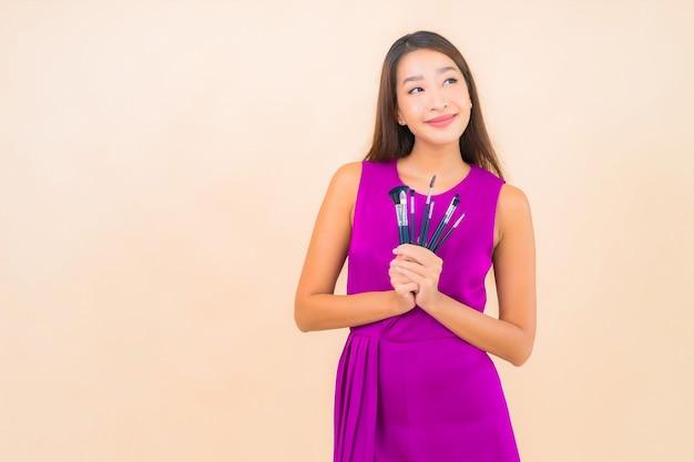 Porträt schöne junge asiatische frau mit make-up pinsel auf farbe lokalisierten hintergrund
