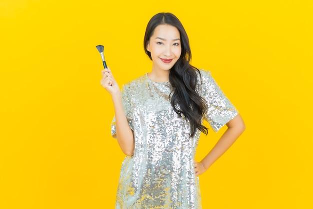 Porträt schöne junge asiatische frau mit make-up pinsel kosmetik auf gelb