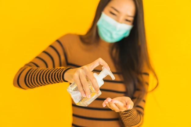 Porträt schöne junge asiatische frau mit maske alkoholspray und gelflasche in der hand zum schutz vor coronavirus oder covid19