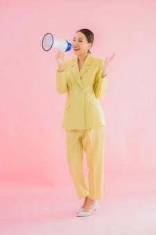 Porträt schöne junge asiatische frau mit megaphon auf farbe