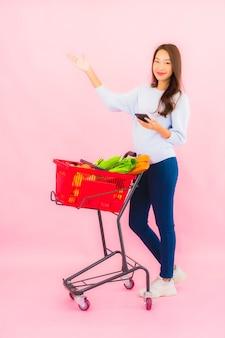 Porträt schöne junge asiatische frau mit obstgemüse und lebensmittelgeschäft im korb auf rosa isolierter wand