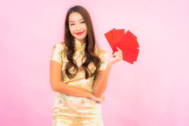 Porträt schöne junge asiatische frau mit roten umschlägen auf rosa wand
