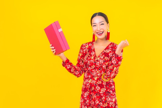 Porträt schöne junge asiatische frau mit roter geschenkbox auf farbwand