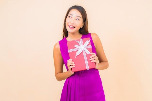 Porträt schöne junge asiatische frau mit roter geschenkbox auf lokalisiertem farbhintergrund