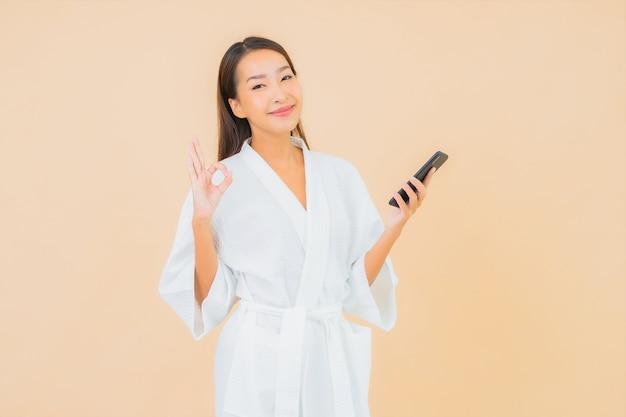 Porträt schöne junge asiatische frau mit smart-handy auf beige