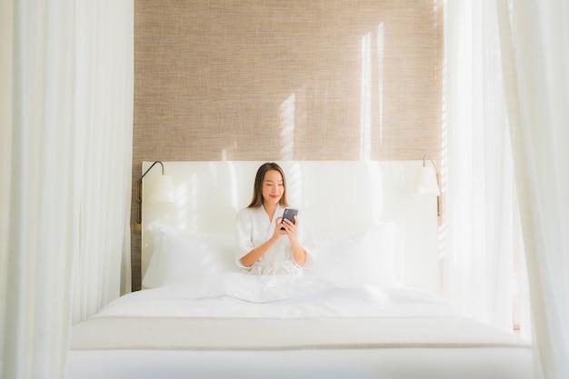 Porträt schöne junge asiatische frau mit smart-handy auf bett im schlafzimmer