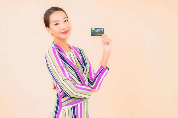 Porträt schöne junge asiatische frau mit smart-handy und kreditkarte auf farbe