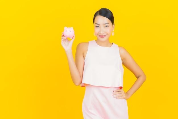 Porträt schöne junge asiatische frau mit sparschwein auf gelb