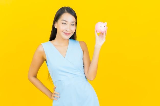 Porträt schöne junge asiatische frau mit sparschwein auf gelber farbwand