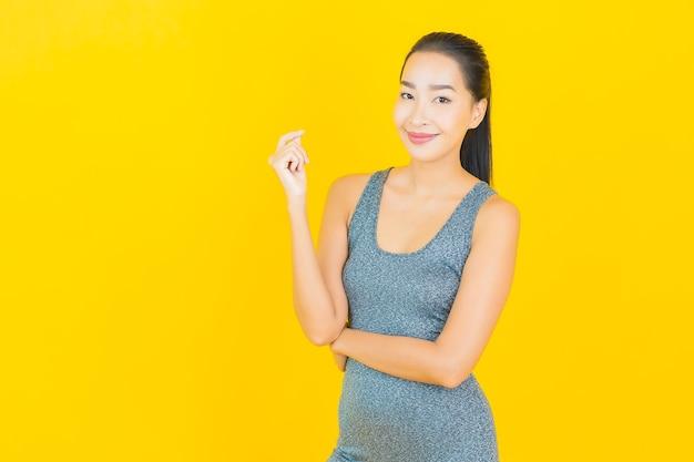Porträt schöne junge asiatische frau mit sportbekleidung bereit für übung auf gelber wand