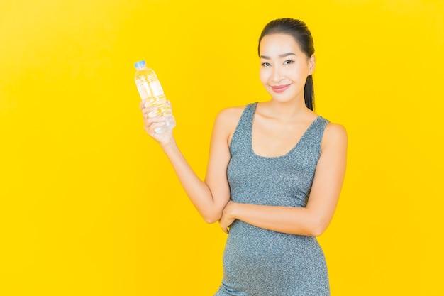 Porträt schöne junge asiatische frau mit sportbekleidung und flaschenwasser auf gelber wand