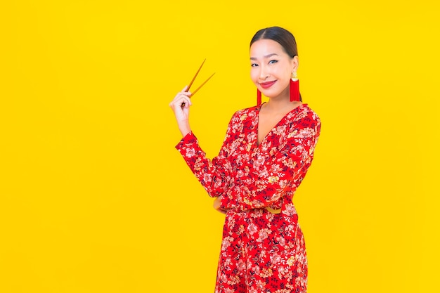 Porträt schöne junge asiatische frau mit stäbchen auf farbe isolierte wand