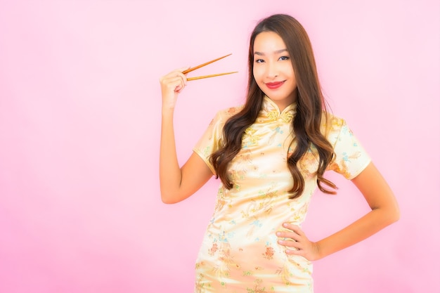 Porträt schöne junge asiatische frau mit stäbchen auf rosa wand